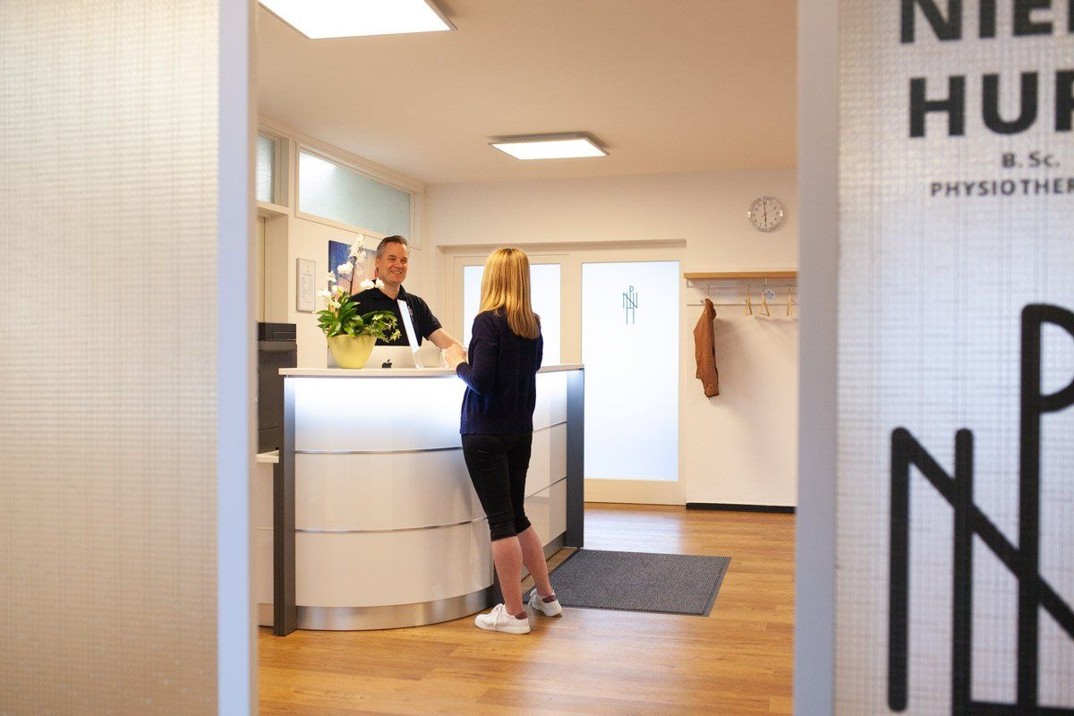 Praxis Niels Hupe Physiotherapie Empfang mit Klientin